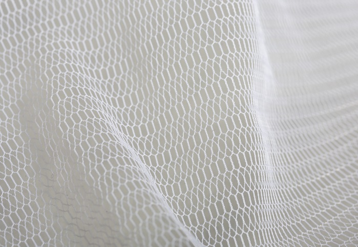 Warp-knitted tulle pattern produced with monofilament yarns on an HKS 3-M. © Karl Mayer