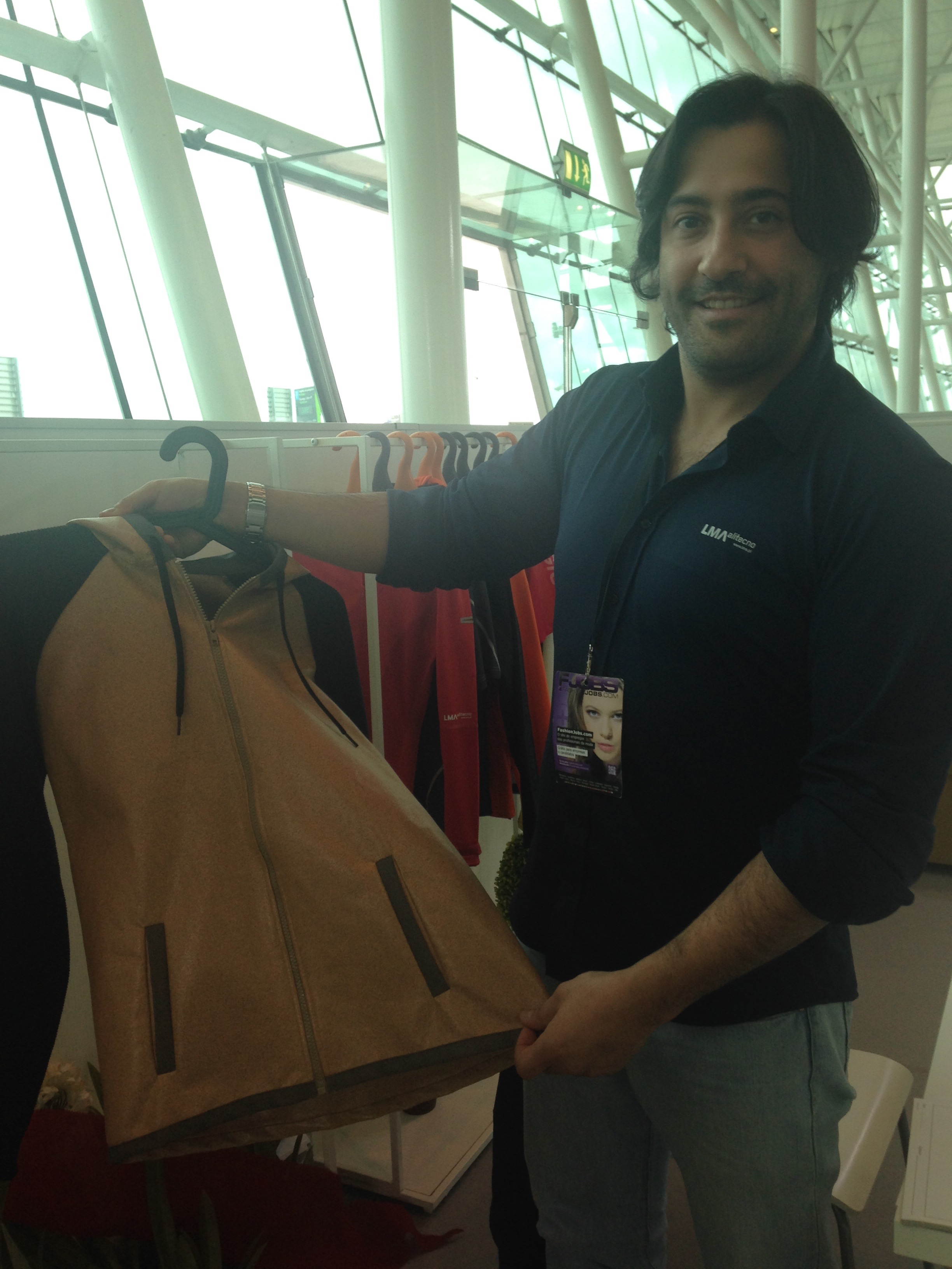 Luis Sousa Dias, of LMA, is holding up a jacket made of a cork based fabric. © Elizia Volkmann