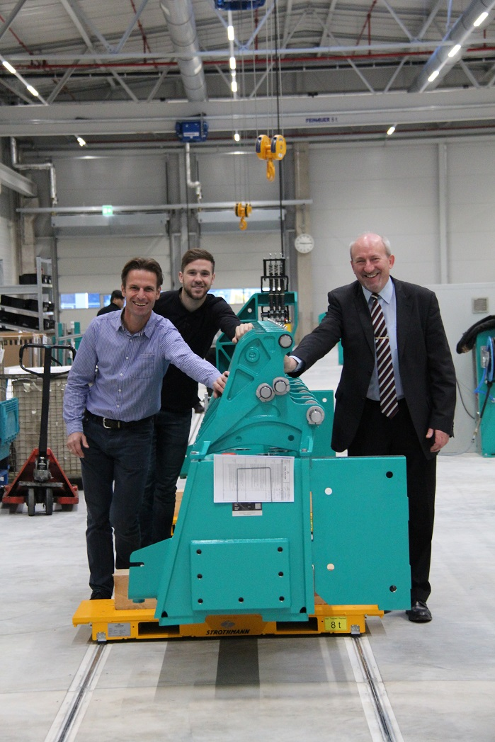 Still done manually but will soon be automated – the Head of the Business Unit, Herbert Lohr (on the right), the Head of Machine Dispatch, Burkhard Reith (front left) and Dominik Marton, an assistant in assembly and logistics, push the first machine on the new assembly line to the next workstation. © Karl Mayer