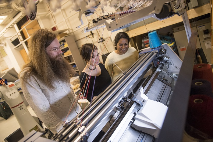 James McCann, Lea Albaugh and Vidya Narayanan watch Shima Seiki's SWG091N2 15-gauge V-bed knitting machine work on a 3D shape. © Carnegie Mellon University