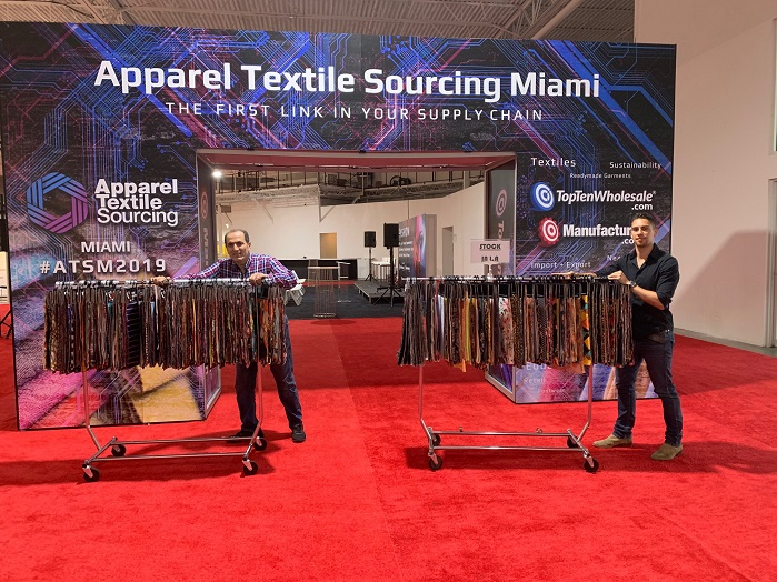 Chase Vance, Director of ATSM, helps exhibitor Sean Zarini, of LA-based Fabric Selection, set up for Apparel Textile Sourcing Miami. © ATSM